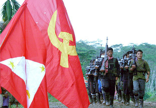 NPA guerrillas march in the background as the infamous Marxist hammer and sickle is displayed.Photo taken from www.inquirer.net