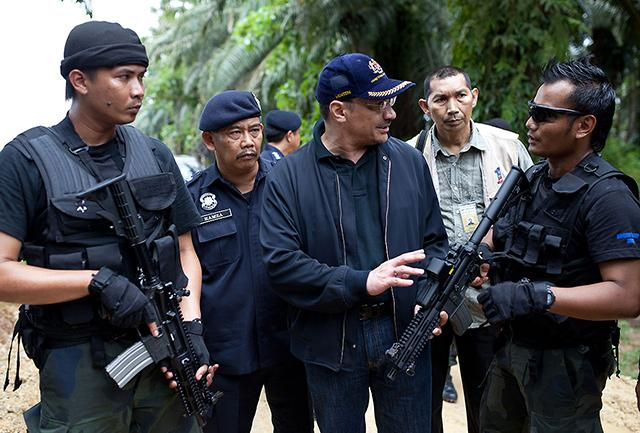 The Malaysian Prime Minister Mohd Najib Razak is briefed by his security forces on the standoff.