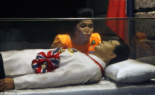Imelda Marcos kissing the glass tomb of her late husband, former Philippine dictator Ferdinand Marcos.
