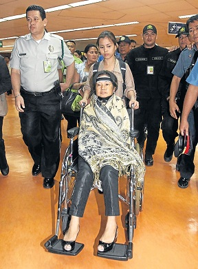 Former president Gloria Arroyo being brought to trial on a wheelchair.