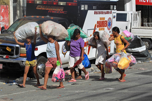A family bring sacks of toys they ransacked from a nearby department store.