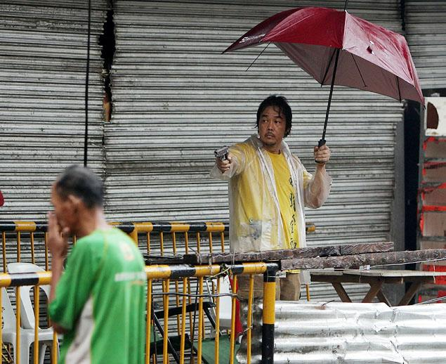A man defends his property with a gun. Calmly pointing it at a passerby while holding an umbrella to stay dry from the rain.
